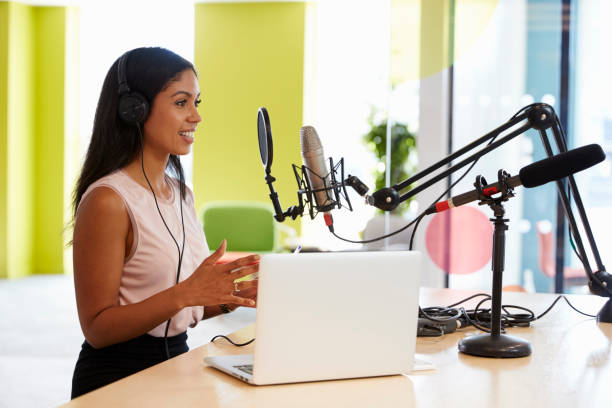 Young mixed race woman recording a podcast in a studio Young mixed race woman recording a podcast in a studio broadcasting stock pictures, royalty-free photos & images