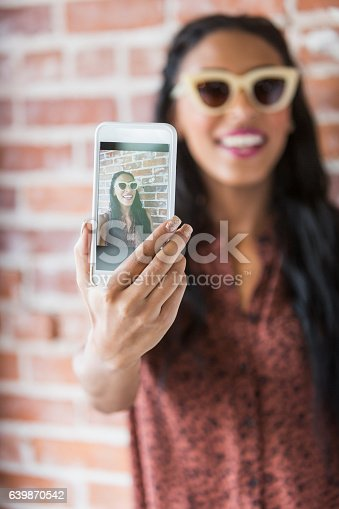 A beautiful young woman, mixed race African ethnicity and Caucasian, taking a selfie.  She is holding her mobile phone in her extended arm.  We can see her image on the screen.  She is wearing sunglasses, standing in front of a brick wall, smiling.  The focus is on the phone.