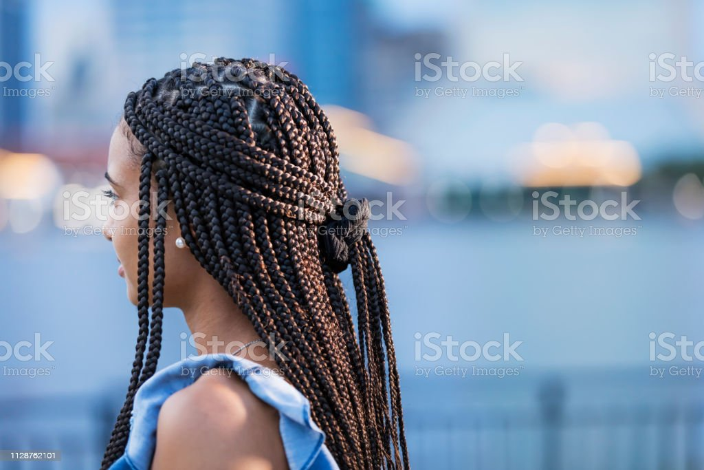 Young mixed race woman with cornrow braids A young mixed race woman in her 20s in the city, standing outdoors on the waterfront. She has beautiful long black hair, cornrow braids tied back with a hair band. 20-24 Years Stock Photo