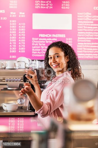istock Young mixed race woman working in coffee shop 1023223934