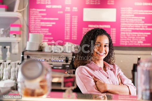 istock Young mixed race woman working in coffee shop 1023224354