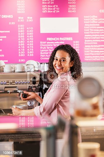 istock Young mixed race woman working in coffee shop 1036473418