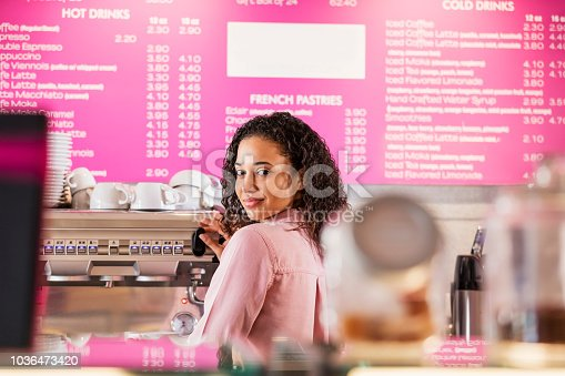 istock Young mixed race woman working in coffee shop 1036473420