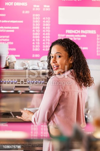 istock Young mixed race woman working in coffee shop 1036475796