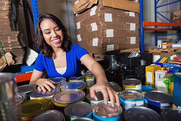 Young mixed-race woman sorting donated groceries in food bank warehouse Young adult Hispanic and Asian woman is smiling as she sorts canned food grocery items. She is volunteering in large food bank warehouse. Woman is volunteering and sorting donations to distribute to community. Large palettes of boxes and food are stacked behind her. food drive stock pictures, royalty-free photos & images