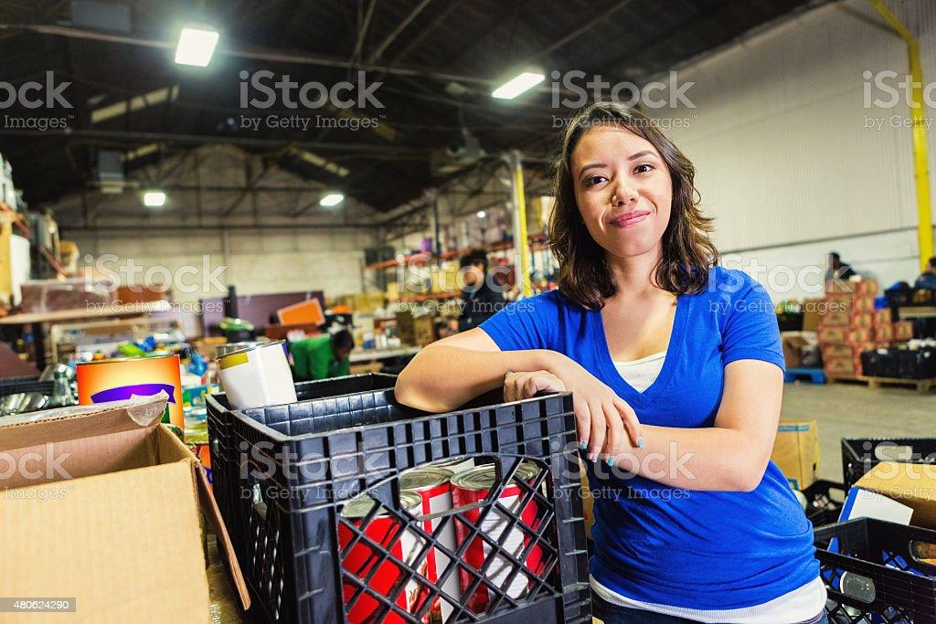 Jóvenes multirraciales mujer en banco de trabajo voluntario para alimentos de almacén - foto de stock