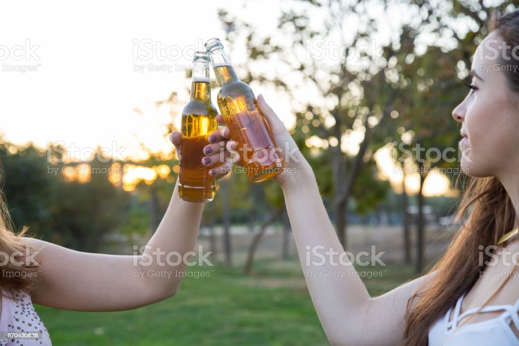 Young Model Celebrating With Beer In Park Stock Photo
