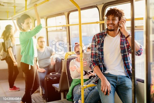 Young modern Afro-American man sitting alone in a public transport and listening to the music. Waiting for bus to move on.