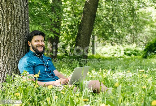 944992706 istock photo Young modern businessman freelancer working on computer and sitting on grass. Male student using notebook outdoors. Tourist working on laptop 1047570808