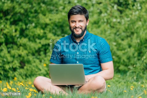 istock Young modern businessman freelancer working on computer and sitting on grass. Male student using notebook outdoors. Tourist working on laptop 1047710878