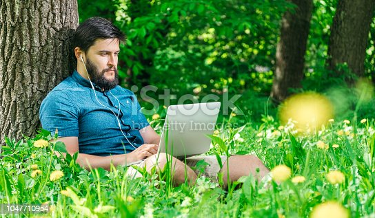 istock Young modern businessman freelancer working on computer and sitting on grass. Male student using notebook outdoors. Tourist working on laptop 1047710954
