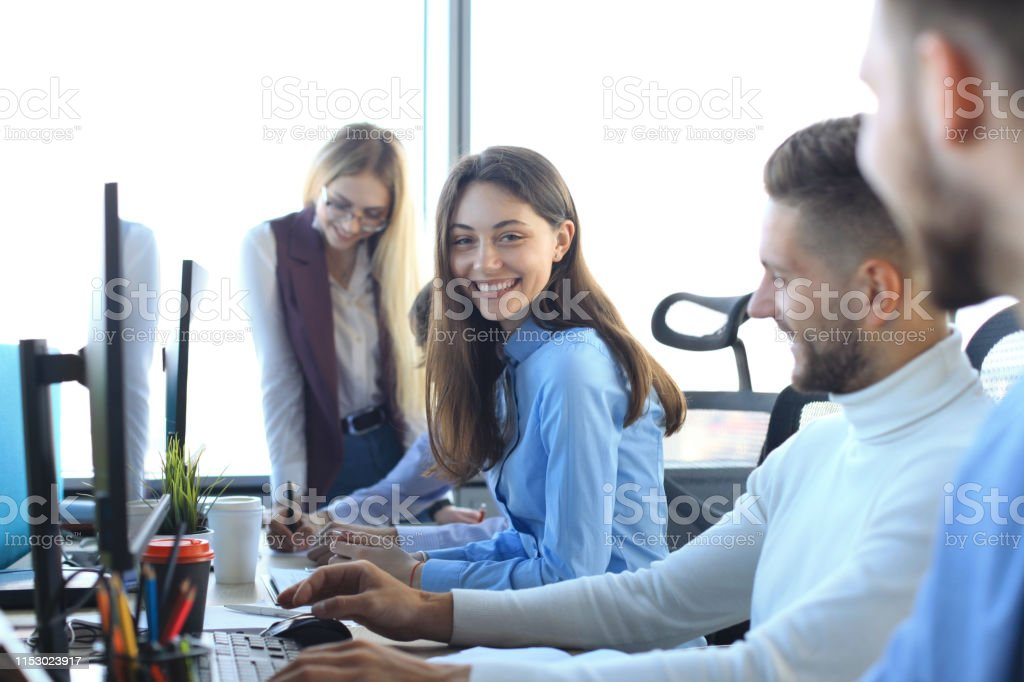 Young modern colleagues in smart casual wear working together while...