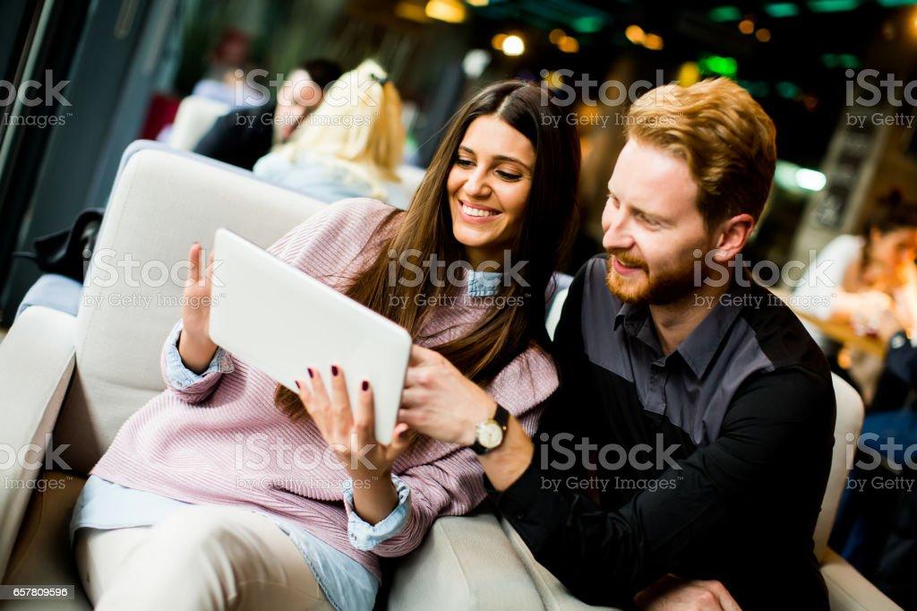 Jovem casal moderno sentados juntos e usando um tablet - foto de acervo