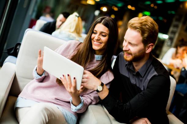 現代の若いカップルが一緒に座っていると、タブレットを使用して ストックフォト