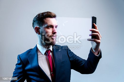 Young modern man in suit using facial recognition softer, modern technology, cyber securit