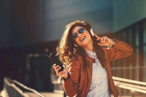 Junge moderne Frau genießt Musik auf der Straße über Kopfhörer – Foto