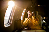 Young fashionable woman sitting on a private airplane and looking through a window while listening to music through headphones.