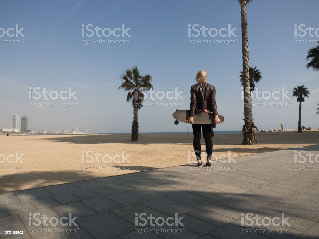 Young modern woman with leather jacket holding a skateboard at the beach in front of a palmtree stock photo