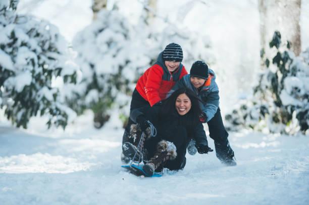 junge mutter und söhne spielen im schnee - schneespiele stock-fotos und bilder