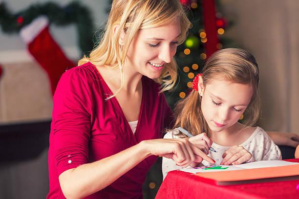 young mom helping daughter make christmas greeting cards - basteln mit kindern weihnachten stock-fotos und bilder