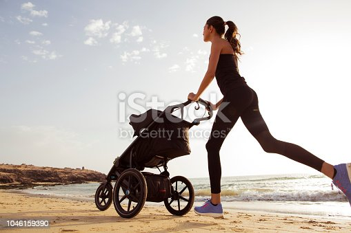 istock Young mom is running with stroller on the beach. 1046159390
