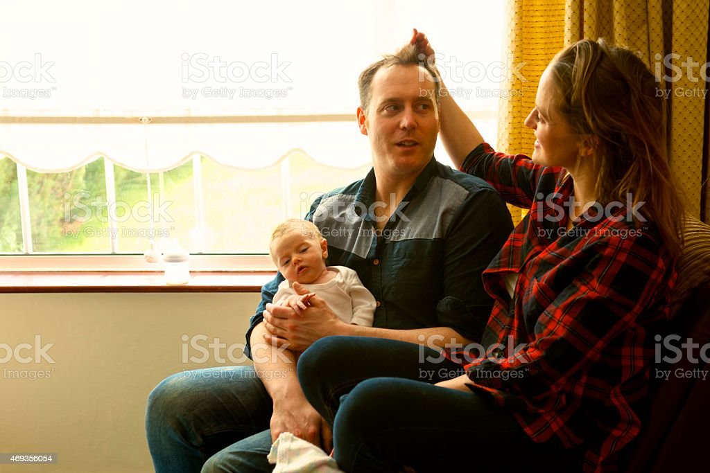 Young Mom Jokes With Hair Dad Sitting With Their Daughter