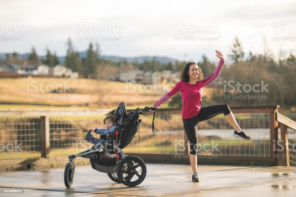 Young mom jumping next to child in baby stroller stock photo