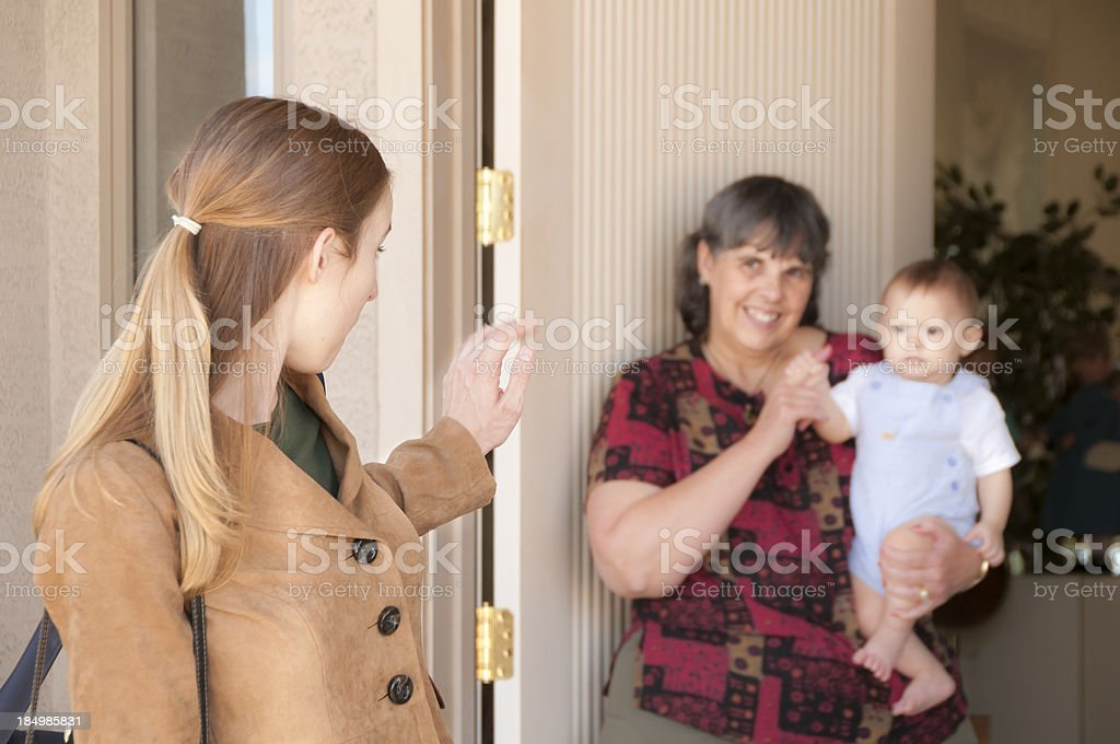 Young Mom Leaves Baby with Sitter stock photo