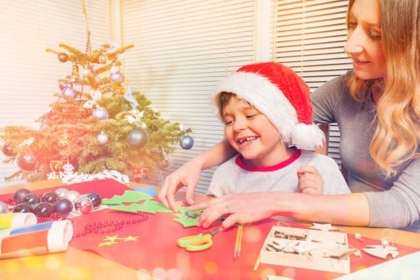 junge mutter macht weihnachtskugeln mit ihrem sohn - winterdeko basteln stock-fotos und bilder