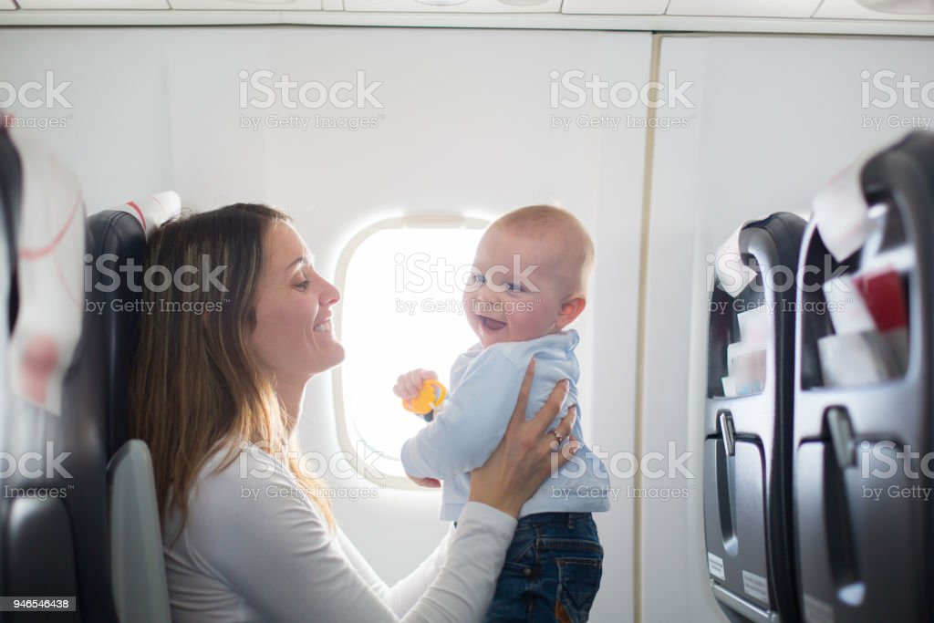 Young mom, playing and breastfeeding her toddler boy on board of aircraft stock photo