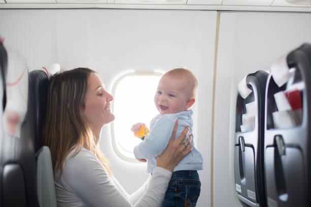 Joven mamá, jugando y lactancia materna su hijo de niño a bordo de las aeronaves - foto de stock