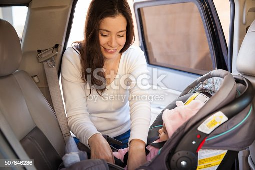 istock Young mom securing a child car seat 507846236