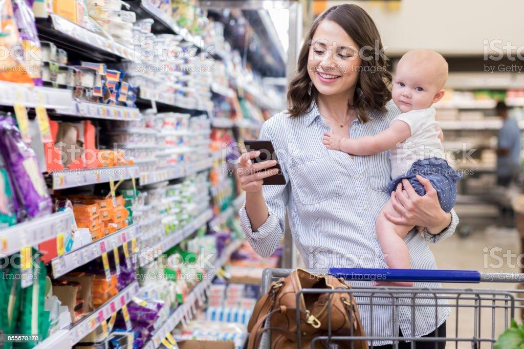 Junge Mutter Geschäfte mit ihrem Baby im Supermarkt – Foto