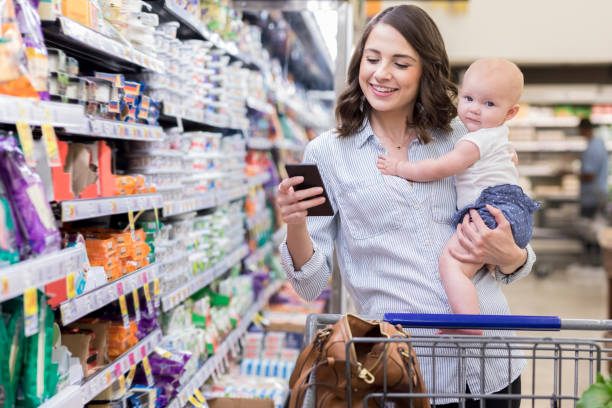 young mom shops with her baby in supermarket - kids phones stock photos and pictures