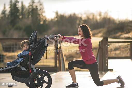 Young Hawaiian mom stretching next to young happy boy in stroller.