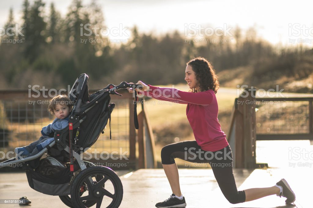 Young mom stretching next to child in baby stroller stock photo