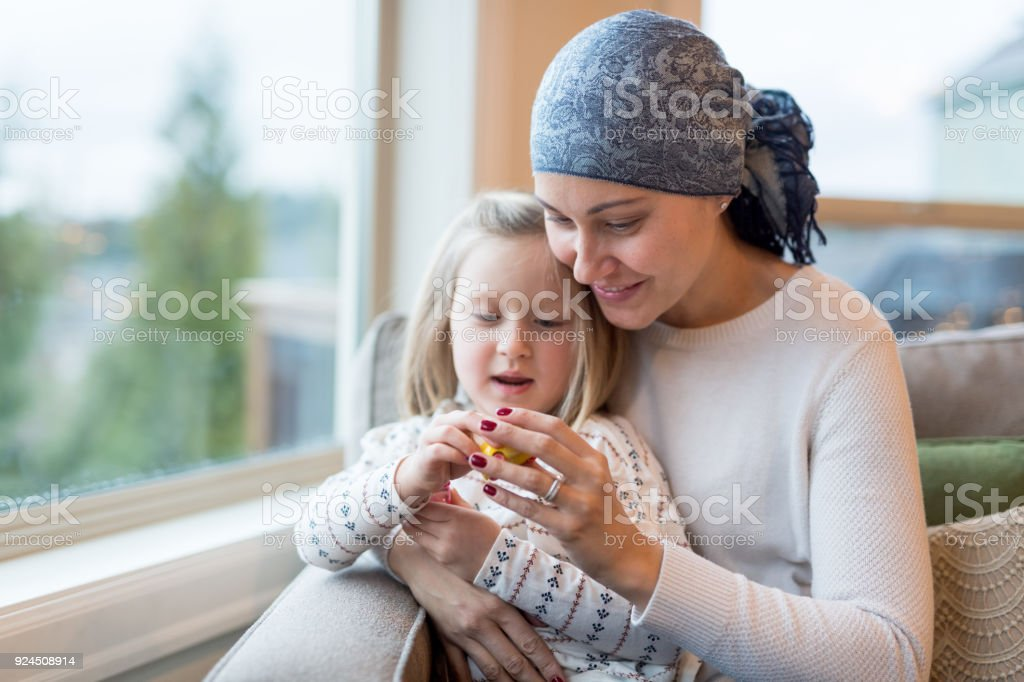 Young ethnic mom with cancer holds her daughter stock photo