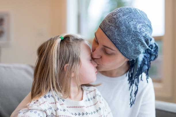 young ethnic mom with cancer holds her daughter - cancer illness stock photos and pictures