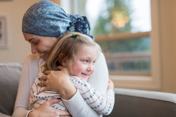 Young ethnic mom with cancer holds her daughter tightly A beautiful young ethnic woman with cancer and wearing a headscarf holds her preschool-age daughter in her lap by their living window. She is squeezing her tight and closing her eyes. Her daughter has a big smile and is hugging her mom affectionately. cancer patient stock pictures, royalty-free photos & images