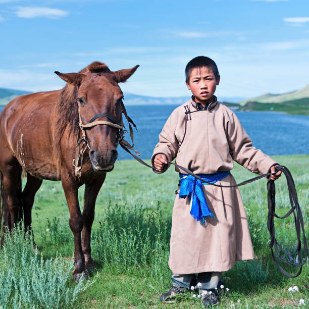 Young Mongolian horseback rider Young Mongolian horseback rider. Lake in the background.http://bem.2be.pl/IS/mongolia_380.jpg mongolian culture stock pictures, royalty-free photos & images
