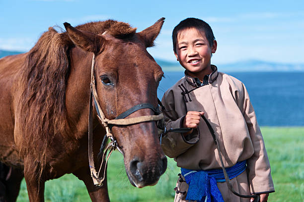 Young Mongolian horseback rider Mongolian horseback rider, lake in the background.http://bem.2be.pl/IS/mongolia_380.jpg mongolian culture stock pictures, royalty-free photos & images