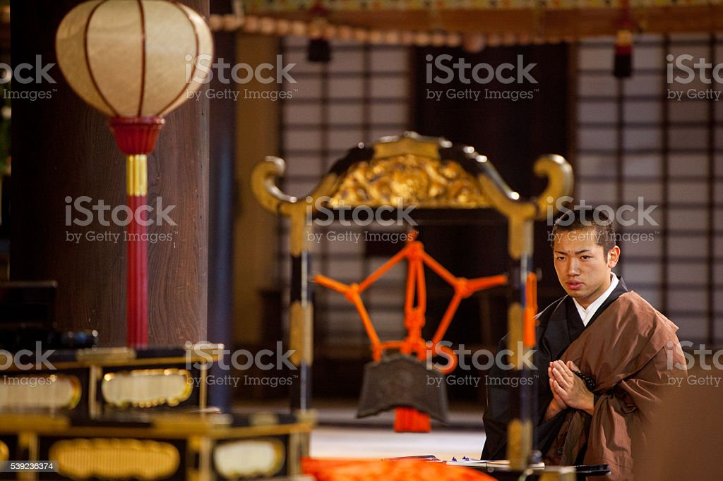 Young monk focused during morning prayer royalty-free stock photo