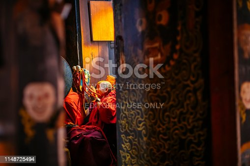 A boy in monks clothing holds a performance mask at the Nirzaegang (Neyzergang) Goempa Festival