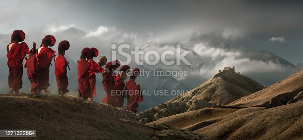 istock Young monks in traditional clothes walk against background of the mountains to an old temple in the kingdom of Mustang, Nepal. 1271322864