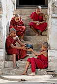 Four young monks from Bagan, Myanmar, sitting on a stairway with a bowl of alms.