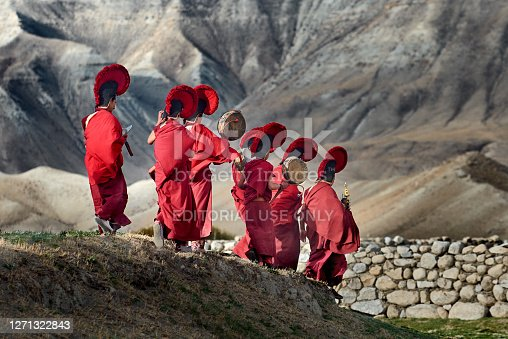 istock Young monks walk against the backround of the mountains to participate in the closing ceremony of the Tigi festival in the capital Lo Mantang of the kingdom of Mustang, Nepal. 1271322843