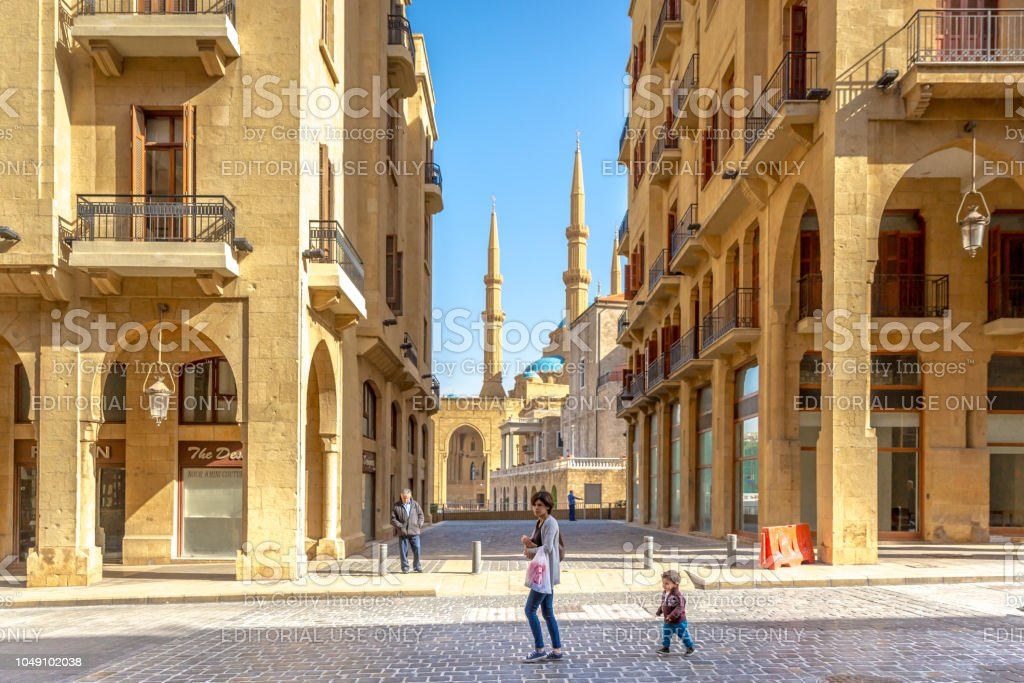 Young mother and a kid walking in the old town of Beirut, mosque in the background, blue sky, Beirut, Lebanon stock photo