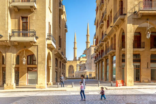 young mother and a kid walking in the old town of beirut, mosque in the background, blue sky, beirut, lebanon - beirut foto e immagini stock