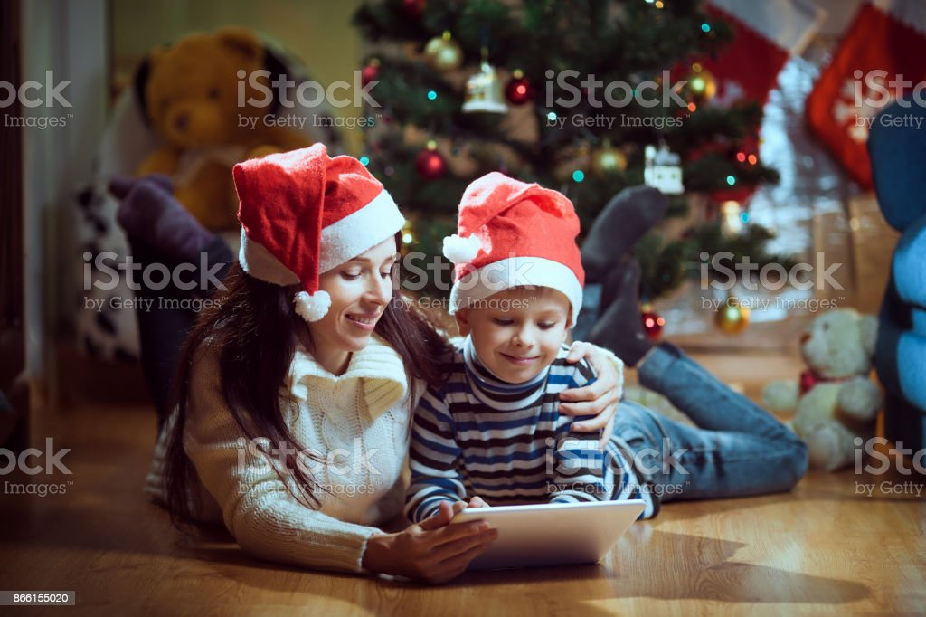 Young mother and a son using a tablet pc by a fireplace on warm Christmas evening stock photo