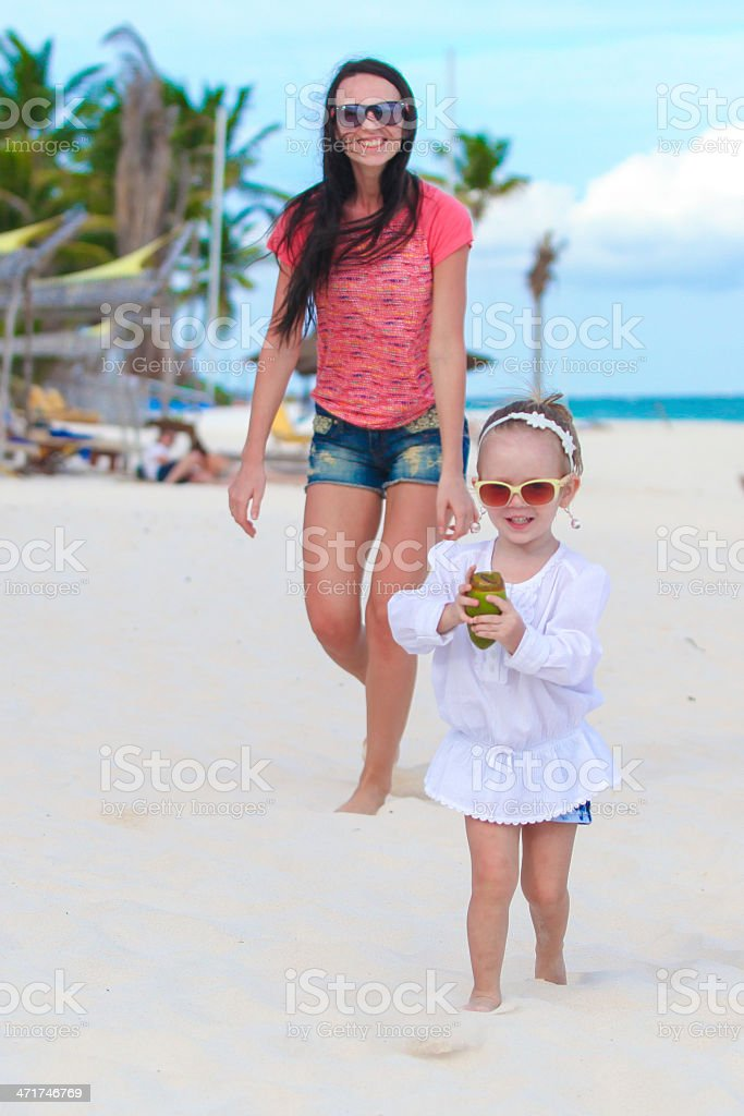 Young mother and adorable daughter running along the sea royalty-free stock photo